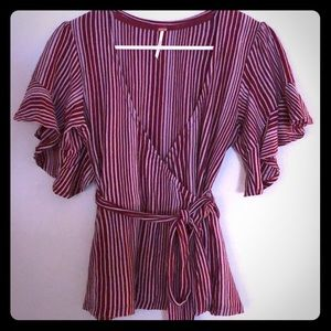 Free People low V wrap blouse with ruffle sleeve.